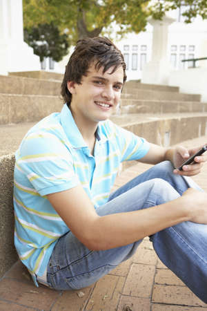 Male Teenage Student Sitting Outside On College Steps Using Mobile Phone Stock Photo - 8108719