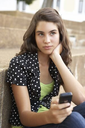 Unhappy Female Teenage Student Sitting Outside On College Steps Using Mobile Phone Stock Photo - 8108706