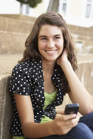 Teenage Student Sitting Outside On College Steps Using Mobile Phone Stock Photo - 8108679