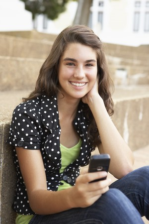 Teenage Student Sitting Outside On College Steps Using Mobile Phone Stock Photo - 8108648