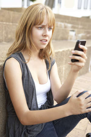 Unhappy Female Teenage Student Sitting Outside On College Steps Using Mobile Phone Stock Photo - 8108695