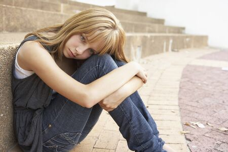 depressed teenager: Unhappy Female Teenage Student Sitting Outside On College Steps Using Mobile Phone