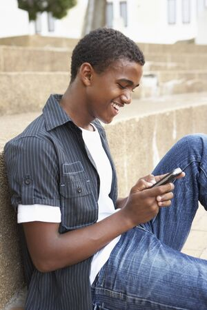 Male Teenage Student Sitting Outside On College Steps Using Mobile Phone photo