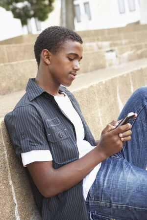 Unhappy Male Teenage Student Sitting Outside On College Steps Using Mobile Phone Stock Photo - 8108731