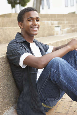 mixed race teen: Smiling Male Teenage Student Sitting Outside On College Steps
