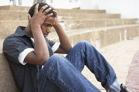 Unhappy Male Teenage Student Sitting Outside On College Steps photo