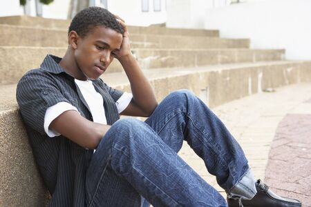 depressed teenager: Unhappy Male Teenage Student Sitting Outside On College Steps