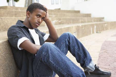 gente triste: Infeliz estudiante adolescente masculino sentado fuera en pasos de College