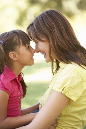 genegenheid: Portret van moeder- en dochter samen In Park  Stockfoto