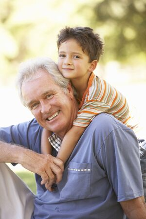 piggyback ride: Grandfather Giving Grandson Ride On Back In Park Stock Photo