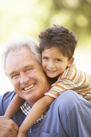 Grandfather Giving Grandson Ride On Back In Park photo
