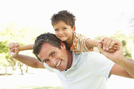 Father Giving Son Ride On Back In Park Stock Photo - 8108537