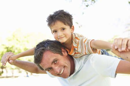 Father Giving Son Ride On Back In Park Stock Photo - 8108551