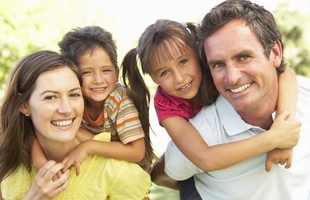 famiglia in giardino: Madre e padre di dare i bambini Piggy Back