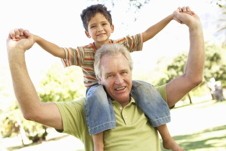 Grandfather Giving Grandson Ride On Back In Park Stock Photo - 8108545