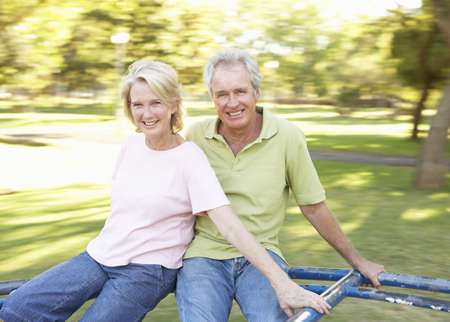 Senior Couple Riding On Roundabout In Park photo