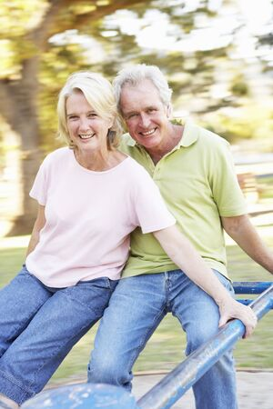 Senior Couple Riding On Roundabout In Park Stock Photo - 8108627