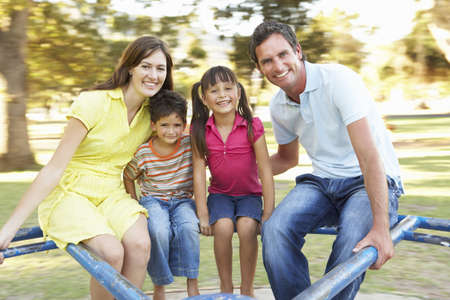 having fun: Family Riding On Roundabout In Park Stock Photo