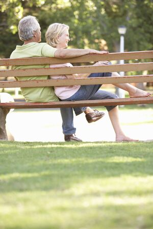 sitting in the bench: Senior Couple Sitting Together On Park Bench Stock Photo