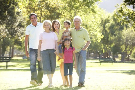 three generation: Extended Group Portrait Of Family Enjoying Walk In Park Stock Photo