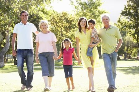 family walking: Extended Group Portrait Of Family Enjoying Walk In Park Stock Photo