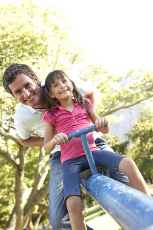 see saw: Father And Daughter Riding On See Saw In Playground
