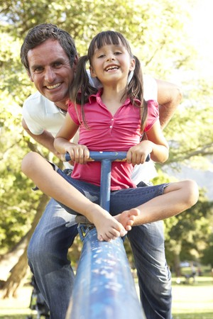 Father And Daughter Riding On See Saw In Playground photo
