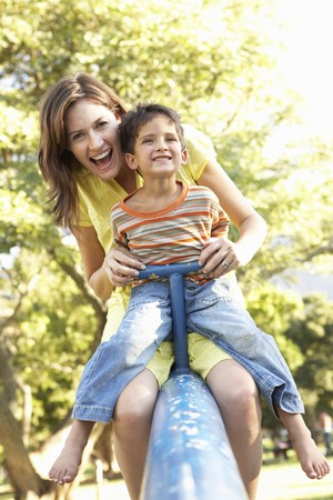 playground equipment: Mother And Son Riding On See Saw In Playground Stock Photo