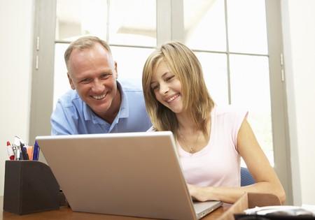 deberes: El padre y la hija adolescente mediante ordenador port�til en casa