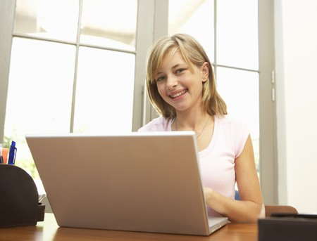 Teenage Girl Using Laptop At Home photo