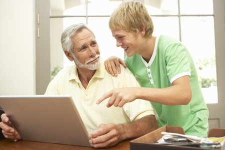 grandkids: Teenage Grandson Helping Grandfather To Use Laptop At Home Stock Photo