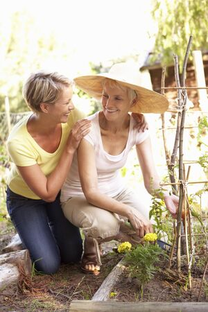 Senior Woman And Adult Daughter Relaxing In Garden photo
