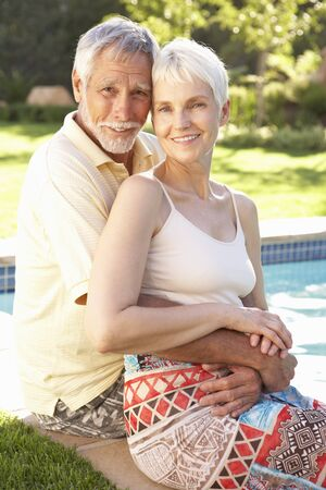 Senior Couple Relaxing By Pool In Garden photo