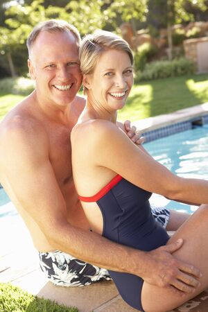 forties: Couple Relaxing By Pool In Garden