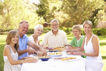 Extended Family Enjoying Meal In Garden photo