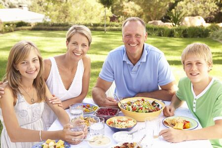 Family Enjoying Meal In Garden photo