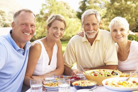 Adult Son And Daughter Enjoying Meal In Garden With Senior Parents photo