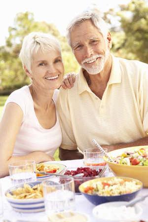 Senior Couple Enjoying Meal In Garden photo
