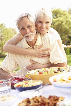 pareja comiendo: Senior pareja disfrutando de la comida en el jard�n  Foto de archivo