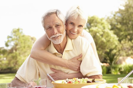 Senior Couple Enjoying Meal In Garden photo