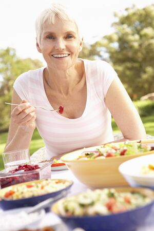 Senior Woman Enjoying Meal In Garden photo