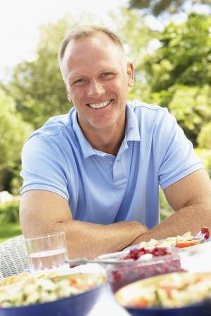 Man Enjoying Meal In Garden photo