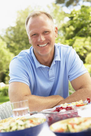40s: Man Enjoying Meal In Garden