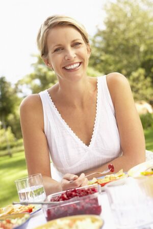 Woman Enjoying Meal In Garden photo