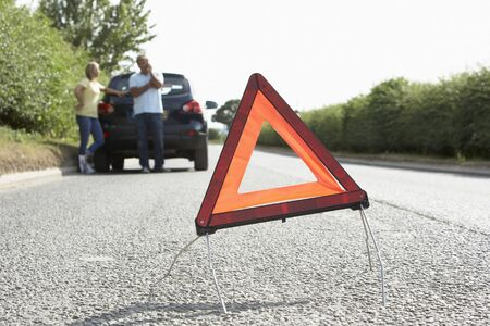 Couple Broken Down On Country Road With Hazard Warning Sign In Foreground photo