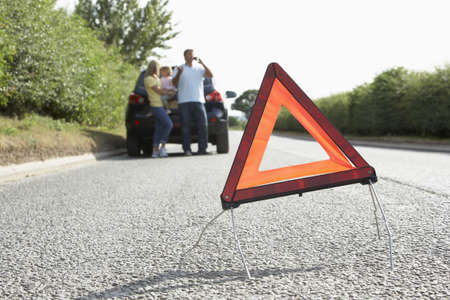 Family Broken Down On Country Road With Hazard Warning Sign In Foreground photo