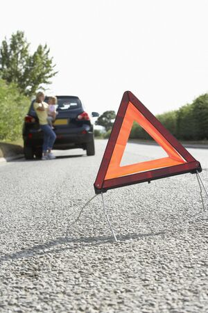 Mother And Daughter Broken Down On Country Road With Hazard Warning Sign In Foreground photo