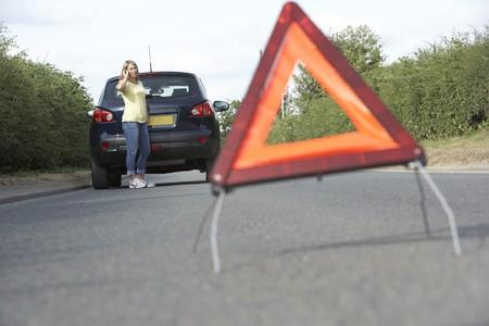 Vrouwelijke bestuurder gebroken Down op land weg met gevaar waarschuwing op voorgrond Stockfoto