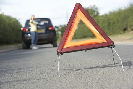 Female Driver Broken Down On Country Road With Hazard Warning Sign In Foreground Stock Photo - 8108846