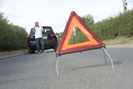 Driver Broken Down On Country Road With Hazard Warning Sign In Foreground photo